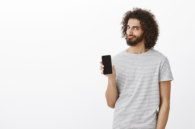 Portrait of satisfied playful eastern bearded man with afro haircut, showing smartphone