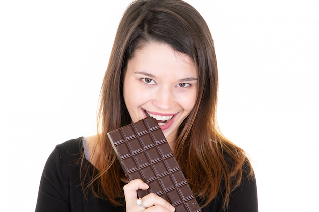 Portrait of a satisfied pretty girl biting chocolate bar smiling