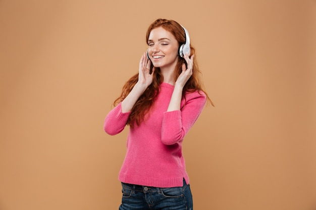 Portrait of a satisfied smiling redhead girl listening music with headphones