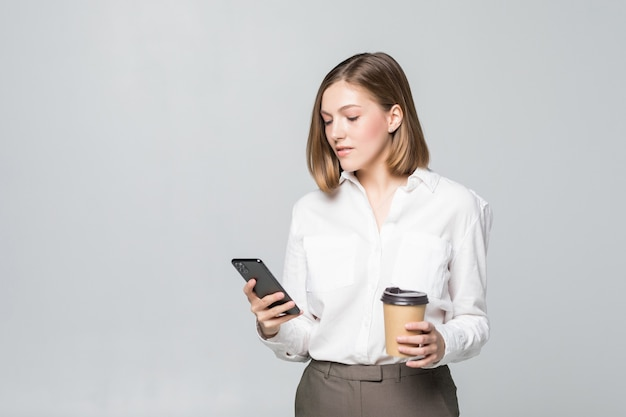 Portrait of a satisfied young business woman using mobile phone while holding cup of coffee to go isolated over white wall