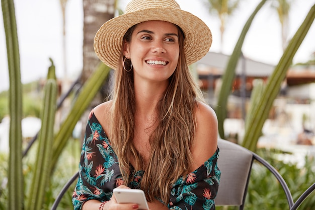 Portrait of satisfied young female with positive expression wears summer hat and stylish blouse, sits on comfortable chair outdoor, holds cell phone, surf social networks, downloads photos on page
