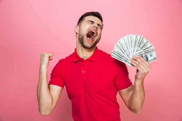 Portrait of a satisfied young man holding money banknotes