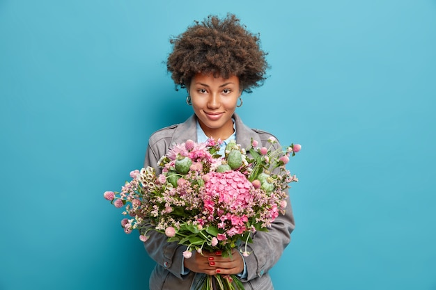 Portrait of satisfied young woman holds nice bouquet of flowers looks confidently at front wears grey jacket isolated over blue wall has pleasant appearance comes on date