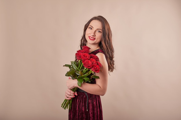 Portrait of satisfied young woman in red dress with bouquet of roses
