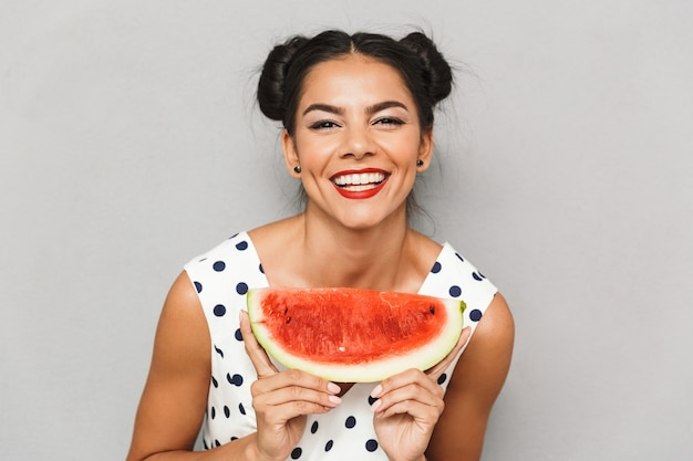 Portrait of a satisfied young woman in summer dress isolated, holding watermelon slice