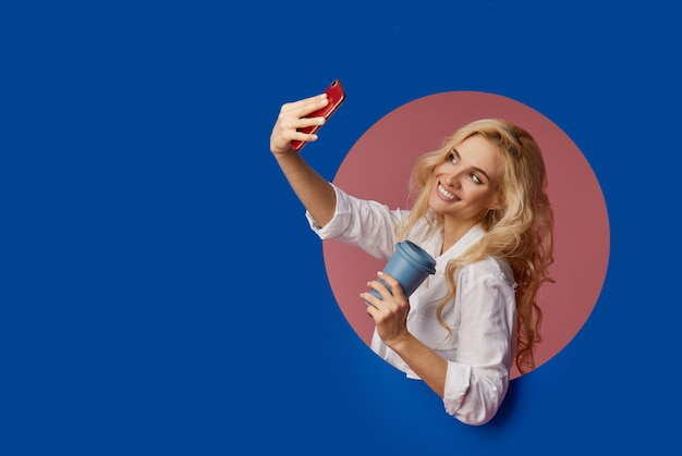 Portrait of a satisfied young woman using mobile phone while holding cup of coffee to go. peeping of the classic blue circle hole in the wall. making selfie and smiling