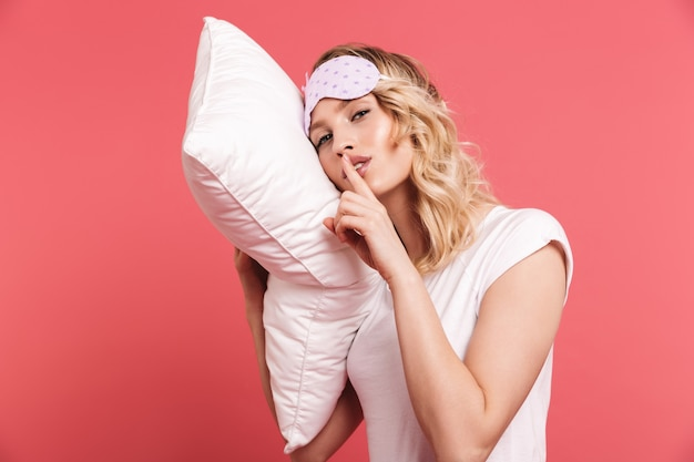 Portrait of satisfied young woman wearing sleeping mask holding and lying on white pillow isolated over red wall