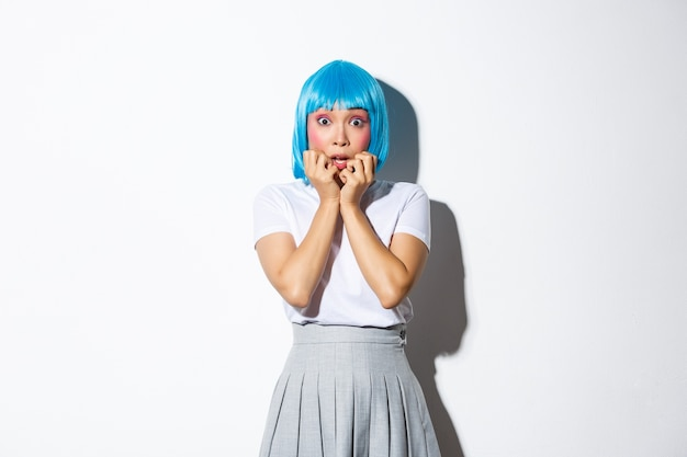 Portrait of scared asian woman gasping afraid, stare at camera ambushed, wearing blue party wig