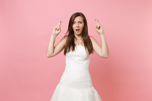Portrait of scared bewildered woman in white dress waiting for special moment, keeping fingers crossed