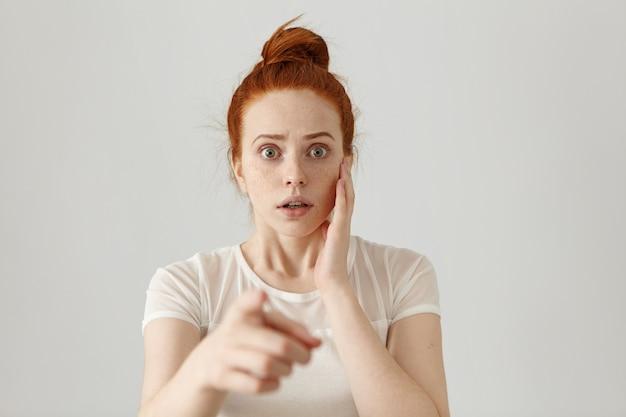 Ritratto di giovane femmina rossa dagli occhi di bug spaventata che ha un'espressione spaventata terrorizzata, spaventata da qualcosa mentre punta il dito indice. pericolo, rischio, accusa o riconoscimento
