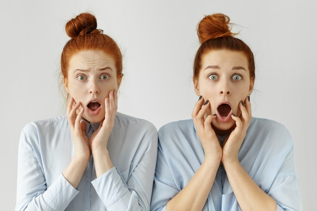 Portrait of scared clueless redhead female office workers wearing same knot hairstyles and formal shirts exclaiming, looking with frightened expression, shocked and terrified with deadline