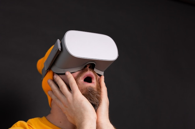 Portrait of scared gamer, man with beard in t-shirt wearing vr glasses on studio  background