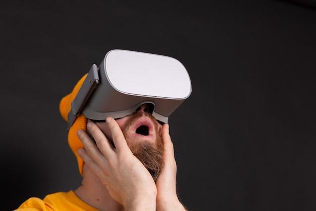 Ritratto del giocatore spaventato, uomo con la barba in t-shirt con gli occhiali vr sullo sfondo dello studio
