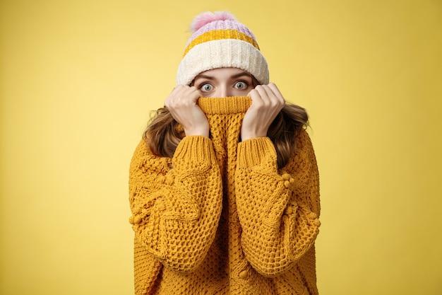 肖像画怖い不安な臆病なかわいい女の子の顔を隠す顔を引っ張るセーターの鼻を広げる目を恐れる冬の帽子をかぶって唖然とした立っている昏迷黄色の背景、おびえた恐怖の寒さ