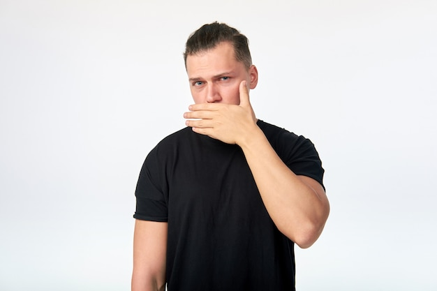 Portrait of scared man covering his mouth with hand.