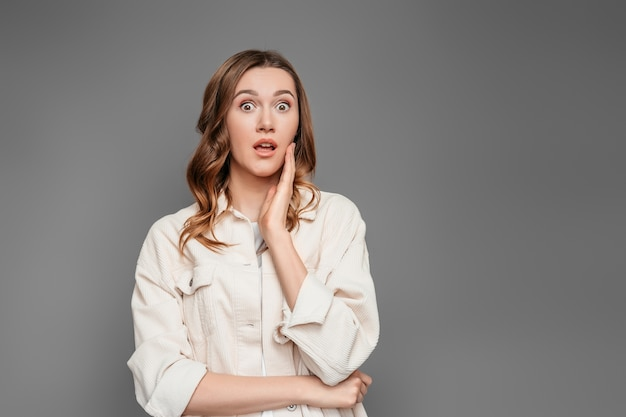 Portrait of scared shocked caucasian young female student isolated on dark grey background in studio