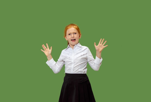 Ritratto della ragazza adolescente spaventata. lei in piedi isolata su sfondo verde alla moda per studio. ritratto femminile a mezzo busto. emozioni umane, concetto di espressione facciale.
