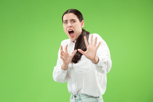 Portrait of the scared woman. business woman standing isolated on trendy green  wall. female half-length portrait. human emotions, facial expression concept