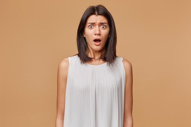 Ritratto di donna spaventata in preda al panico nervoso spaventato vestito in abito bianco, la bocca aperta suscita paura, isolato