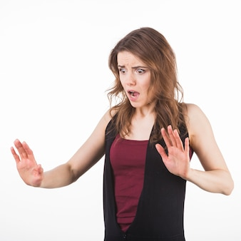 Portrait of scared woman raising hands up in defense