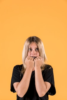 Portrait of scared woman standing against yellow background