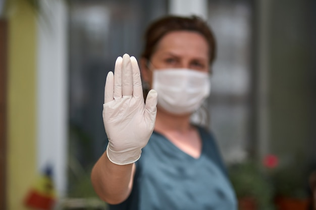 Portrait of scared women showing sign no, crossing arms, keeping distance, wearing antibacterial mask and gloves, looking directly at camera, being in quarantine.