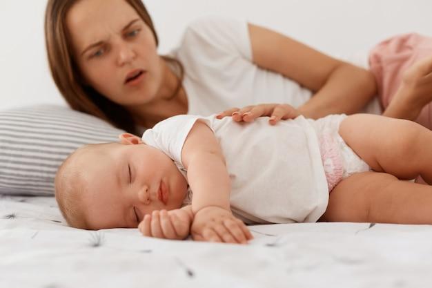 Ritratto di madre preoccupata spaventata guardando la sua piccola figlia addormentata, toccando il bambino, femmina con i capelli scuri che indossa una maglietta bianca in stile casual, maternità.