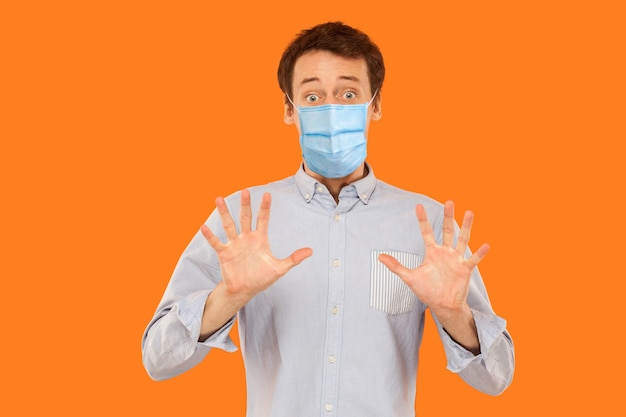 Portrait of scared young worker man with surgical medical mask standing blocking with hands and looking at camera with shocked afraid face. indoor studio shot isolated on orange background.