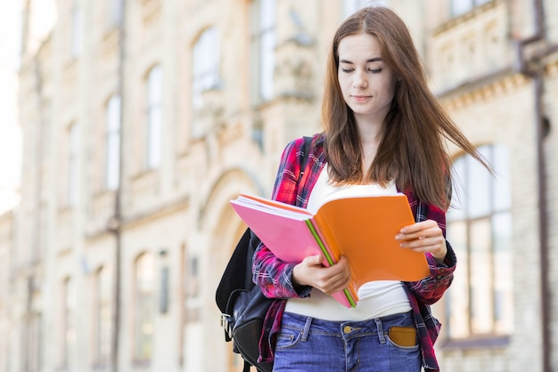 Portrait of school girl with book in city