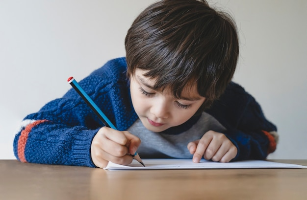 Portrait of school kid boy siting on table doing homework, child holding pencil writing