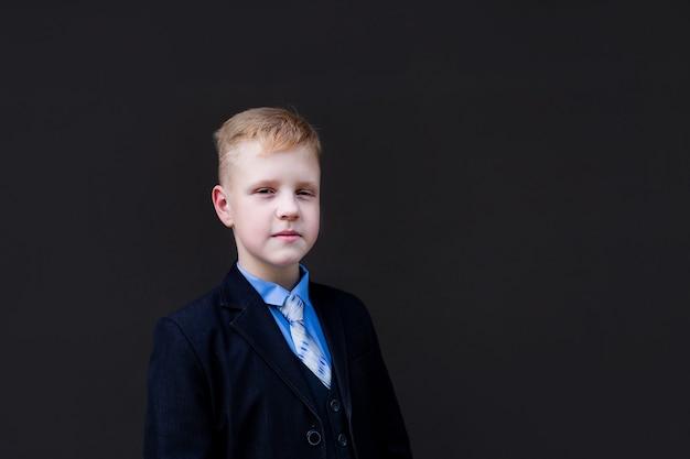 Portrait of a schoolboy against a black wall
