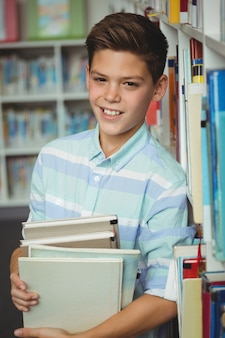 Portrait of schoolboy holding books in library