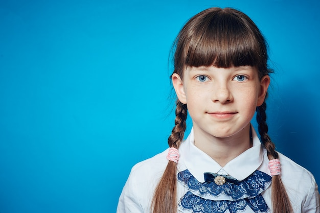 Portrait of a schoolgirl girl on a blue background