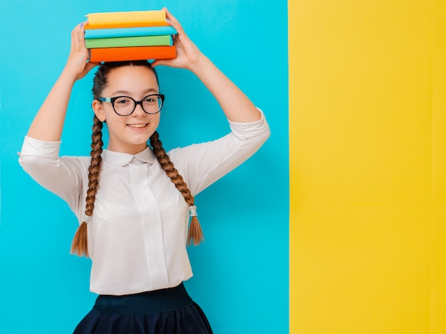 Portrait of a schoolgirl in glasses with books textbooks on yellow blue