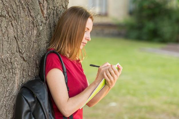 Portrait of schoolgirl leaning against tree