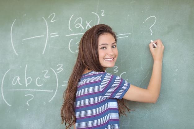 Portrait of schoolgirl pretending to be a teacher in classroom