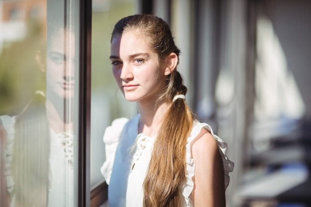 Portrait of schoolgirl standing near window in classroom