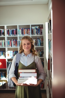 Portrait of schoolgirl standing with stack of books in library