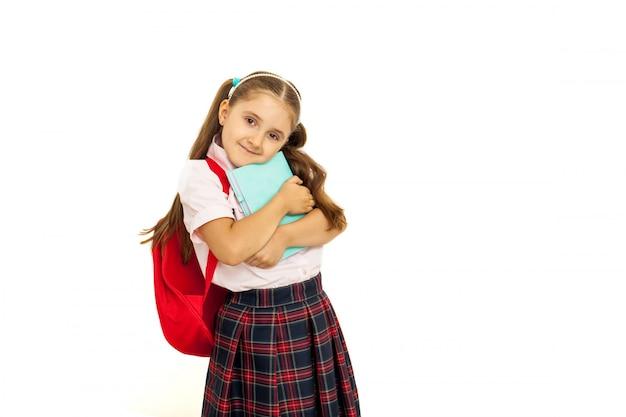 Portrait of a schoolgirl in uniform standing on white background