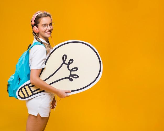 Portrait of schoolgirl with big light bulb