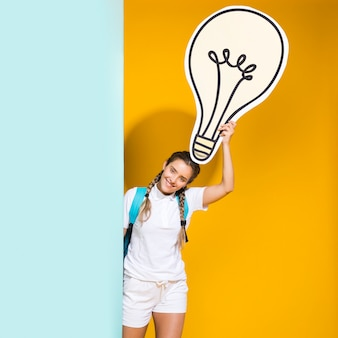 Portrait of schoolgirl with big light bulb