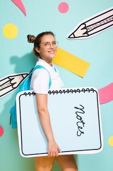 Portrait of schoolgirl with big notepad template