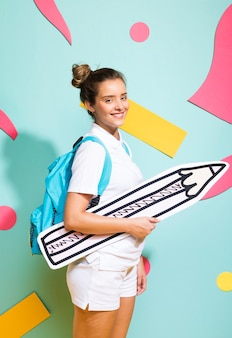 Portrait of schoolgirl with big pencil