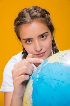 Portrait of schoolgirl with a globe