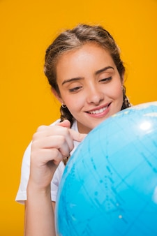 Portrait of schoolgirl with a globe