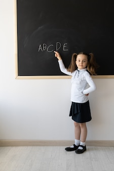Portrait of a schoolgirl with pigtails, learning the alphabet