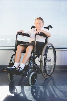 Portrait of schoolkid sitting on wheelchair