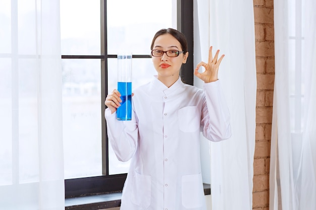Portrait of scientist woman in lab coat holding chemical blue liquid and doing ok sign .