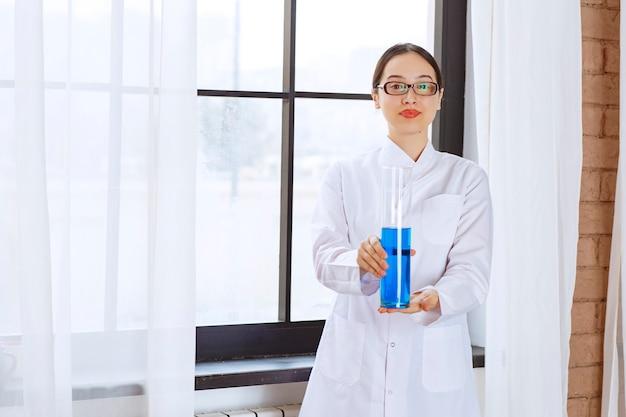 Portrait of scientist woman in lab coat holding chemical blue liquid .