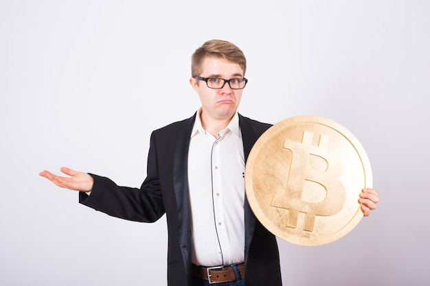 Portrait of a screaming businessman holds big golden bitcoin in his arms. man in panic of cryptocurrency crash.